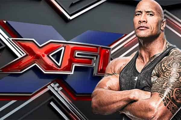 the Rock posing in front of XFL logo